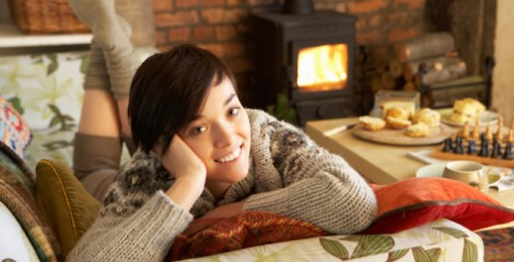 Young woman relaxing by fire